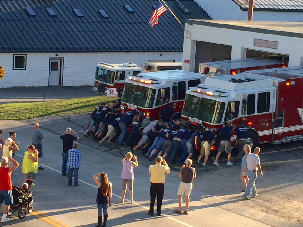 Monmouth firefighters push the department's two new engines into the station Thursday as part of a ceremony to officially place the vehicles into service. More than 30 fire department members helped with the push-in.