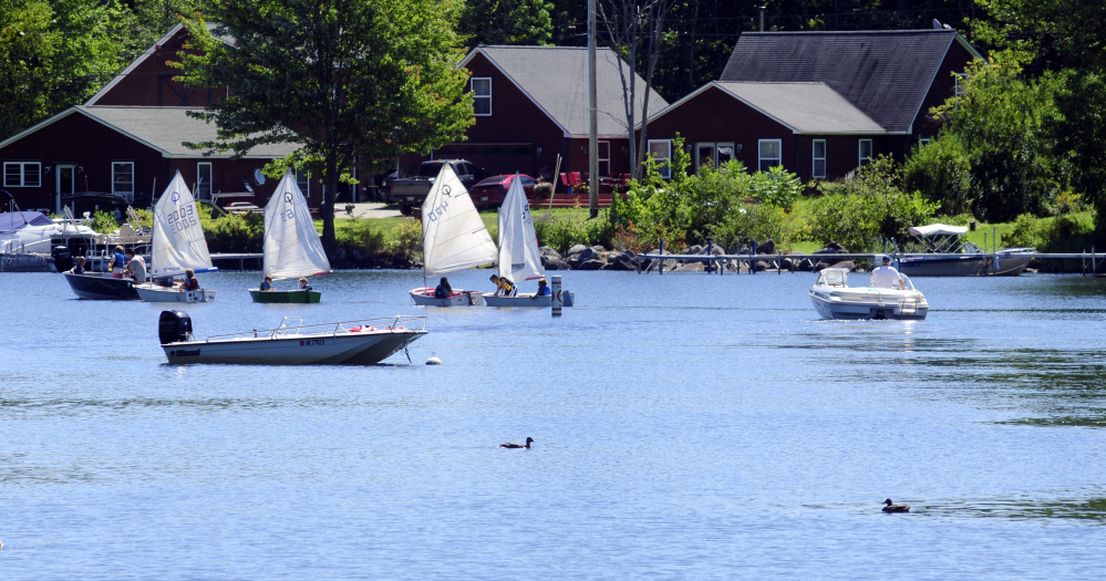 Boats go through the channel on Friday in Mill Stream in Belgrade Lakes.