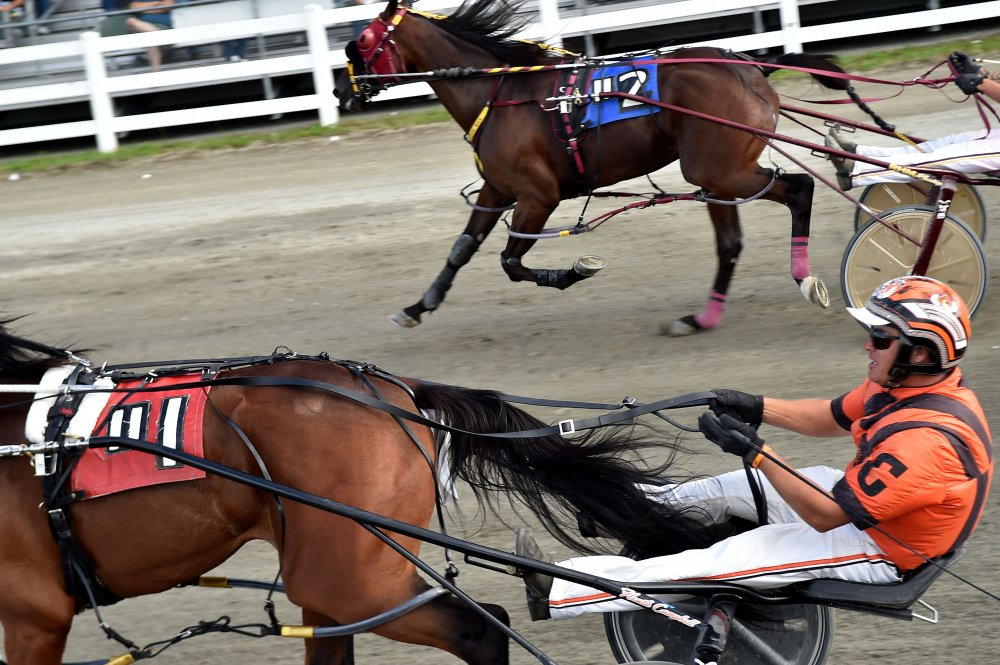 Heath Campbell, bottom, races Bet You (#1) to beat Ron Cushing, racing Escape The News (#2), in a photo finish to win the Walter H. Hight Memorial Pace at the Skowhegan Fairgrounds in  Skowhegan on Saturday.