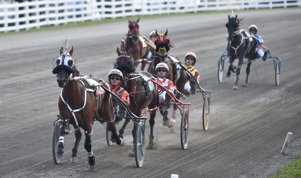 Horses race down the track in the first half mile of the Walter H. Hight Memorial Pace at the Skowhegan Fairgrounds in Skowhegan on Saturday.