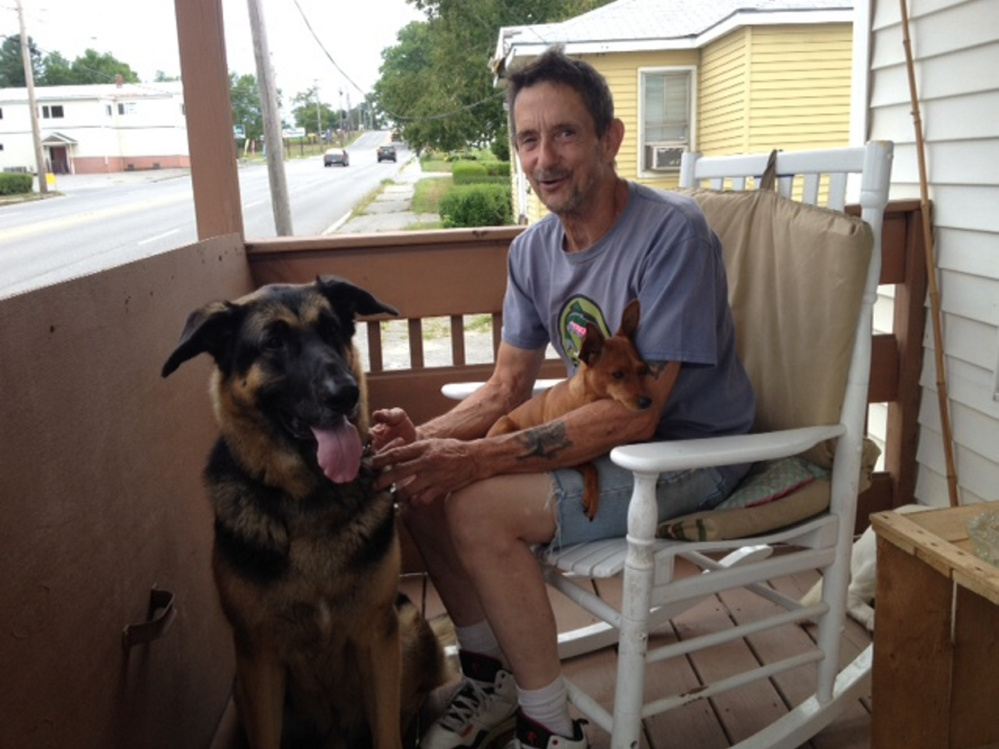 Gary Prentiss, 61, sits on the porch of his new home on Kennedy Memorial Drive in Waterville with his German shepherd, Mack, and miniature pinscher, Ginger. After having a tough time finding a place that would take his several animals, Prentiss was able to rent the house next door to his former house, which is in the background.