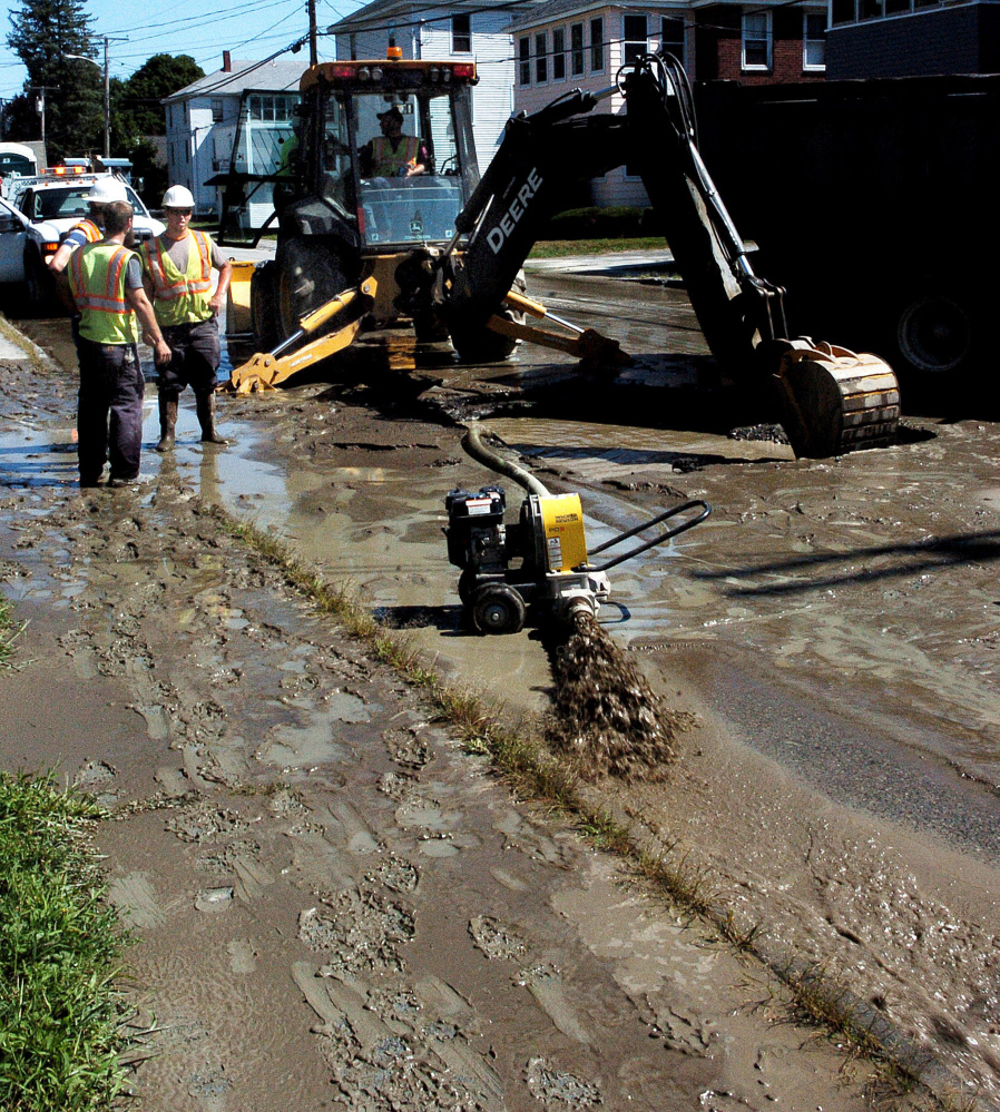 Silty water is pumped from a large hole in Clinton Avenue in Winslow after a water main break on Sunday. The roadway was flooded and traffic was detoured around the scene as crews from Kennebec Water District made repairs.