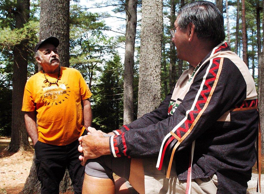 Abnaki tribe member Tom Obomsawin, left, and Penobscot tribe elder Butch Phillips speak Sunday about Native American culture prior to a ceremony honoring ancestors and tribe members that were massacred in 1724 in The Pines area off the Father Rasle Road in Madison.
