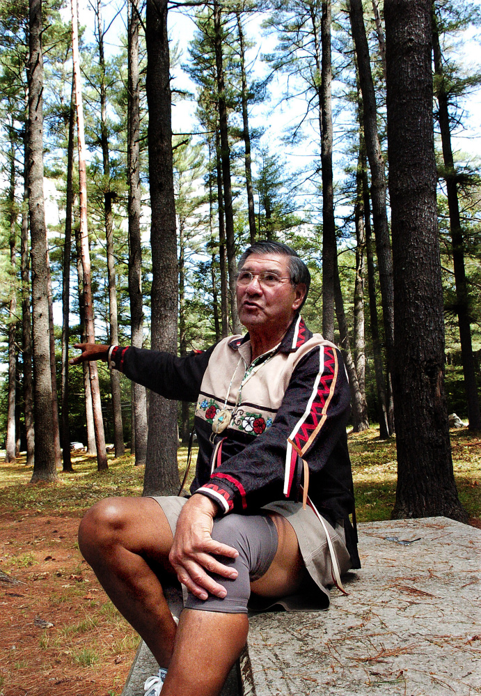 Penobscot tribe elder Butch Phillips speaks prior to a ceremony honoring ancestors on Sunday in The Pines area off the Father Rasle Road in Madison where native Americans were massacred in the 1724.