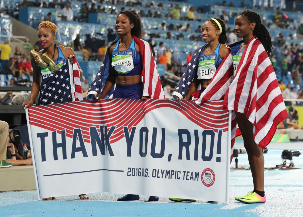 United States' Courtney Okolo, Natasha Hastings, Phyllis Francis and Allyson Felix hold a sign and wear their nation's flag after winning the gold in the women's 4x400 meter relay during athletics competitions at the Summer Olympics inside Olympic stadium Saturday in Rio de Janeiro, Brazil.