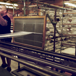 OriginUSA owner Peter Roberts talks about buying used equipment, like this loom, for his manufacturing plant in Industry, which makes jiu jitsu garments.