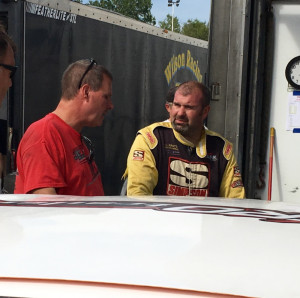 Johnny Clark, of Hallowell, right, talks about his car's performance with Joel Tozier during a practice session for the Pro All Stars Series race at Oxford Plains Speedway in on Aug. 1. The six-time series champion seeks his first Oxford 250 win this Sunday.