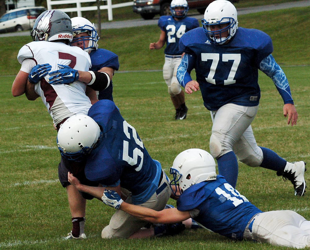 Madison football players gang up and tackle a ball carrier during a scrimmage in Pittsfield on Monday.