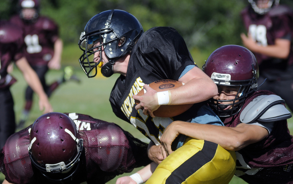 A Maranacook ball carrier gets tackled by a Nokomis defender during a scrimmage Monday afternoon in Readfield.