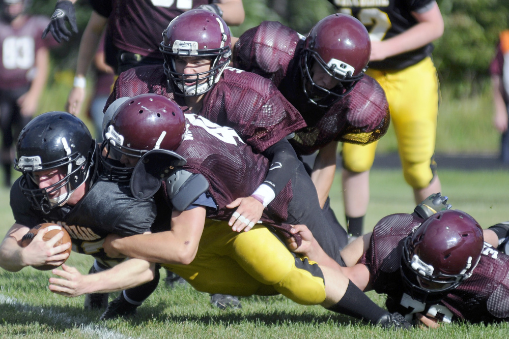 A Maranacook ball carrier gets tackled by a host of Nokomis defenders during a scrimmage Monday afternoon in Readfield.