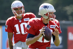 "New England quarterback Tom Brady gets set to throw a pass as quarterback Jimmy Garoppolo watches during an Aug. 9 practice in Foxborough, Massachusetts. Brady says he's ready to play after a ""silly accident"" cut his right thumb with a pair of scissors before a preseason game against the Bears last week."