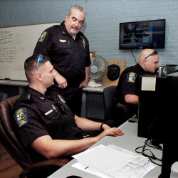 Skowhegan Police Chief Don Bolduc, center, oversees officers C.J. Vera, left, and Ian Shalit filling out reports in June. The selectmen Tuesday night accepted Bolduc's resignation so he can accept retirement benefits from the Maine Public Employees Retirement system and then rehired him as full-time chief.