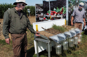 Greg Granger, left, and Peter Abello, of the U.S. Department of Agriculture, using a rainfall simulator, explain on Wednesday how a variety of crop covers ranging from plain soil to grass can yield varying amounts of water absorption rates at the two-day Maine Farm Days event at the Misty Meadows Farm in Clinton.