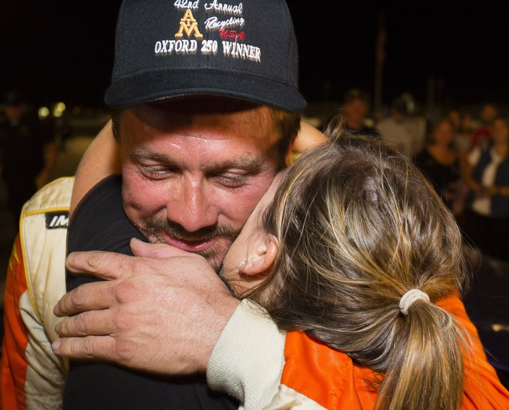 Glen Luce, of Turner, receives a congratulatory hug at the finish line after winning the Oxford 250 at Oxford Plains Speedway last year.