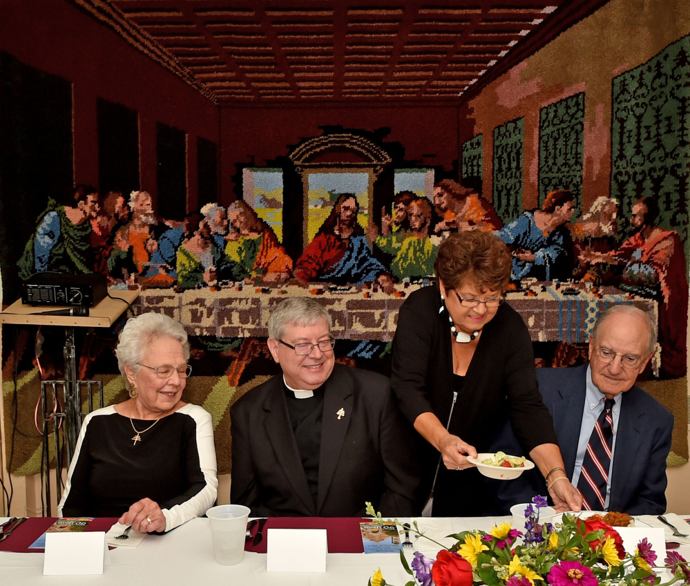 Former U.S. Sen. George Mitchell, right center, receives his meal at the head table during an endowment fund dinner at St. Joseph's Maronite Church in Waterville on Wednesday.