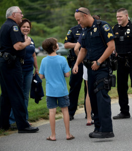 Kryton Smedberg get a fist bump from Waterville Police Department's Sgt. Brian Gardiner during a police appreciation barbecue at Woodlands Senior Living in Waterville on Thursday.