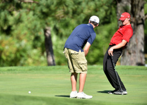 Cony High School's Tyler Dostie, right, uses a little body english to help Mt. Blue High School's Ryan Nelson sink a putt on the fourth green in a season-opening meet at Wilson Lake Country Club in Wilton on Friday.