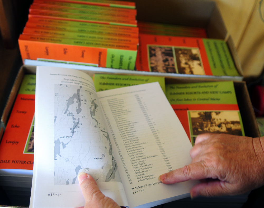 Dale Potter-Clark talks about the map and camps in the front of her recently published book Wednesday at her Vassalboro home.