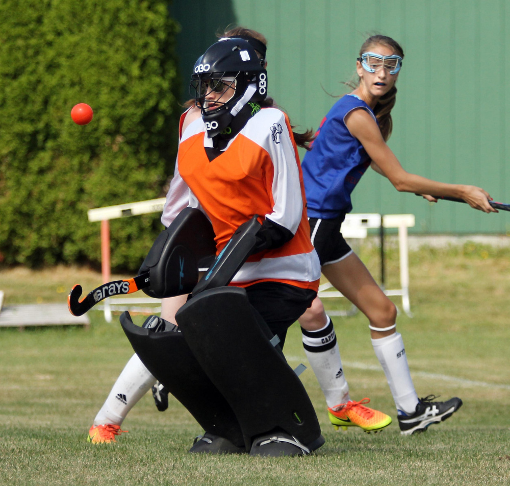 Gardiner Area High School goalie Avery Backus keeps her eyes on the ball as Messalonskee High School's Megan Quirion looks back at the play during a field hockey scrimmage in Winslow on Saturday.
