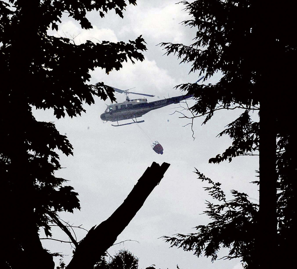 A Maine Forest Service helicopter dumps water over a woods fire Tuesday off Gray Road in Vassalboro. The fire, which was in a hard-to-reach area, burned until Wednesday morning.