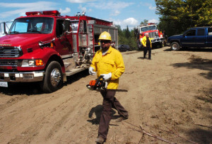 Firefighters from several area departments responded to a woods fire Tuesday off Gray Road in Vassalboro. Winslow Fire Department Assistant Chief Charles Theobald, background, directs trucks to the scene. The fire, which burned until Wednesday morning, was sparking by logging equipment and fueled by dry conditions, a forest ranger said Wednesday.