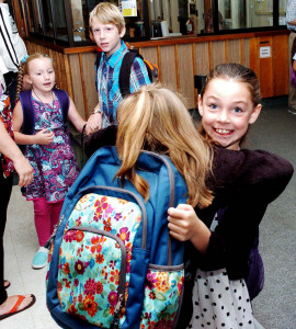 George J. Mitchell School students Raelynn Lacroix, left, and Meena Hall hug each other on their arrival for the first day of school Wednesday in Waterville. Both girls said they were happy to start the school year. Elementary and middle schools across the region welcomed students back Wednesday, while many in grades 10 to 12 start Thursday.
