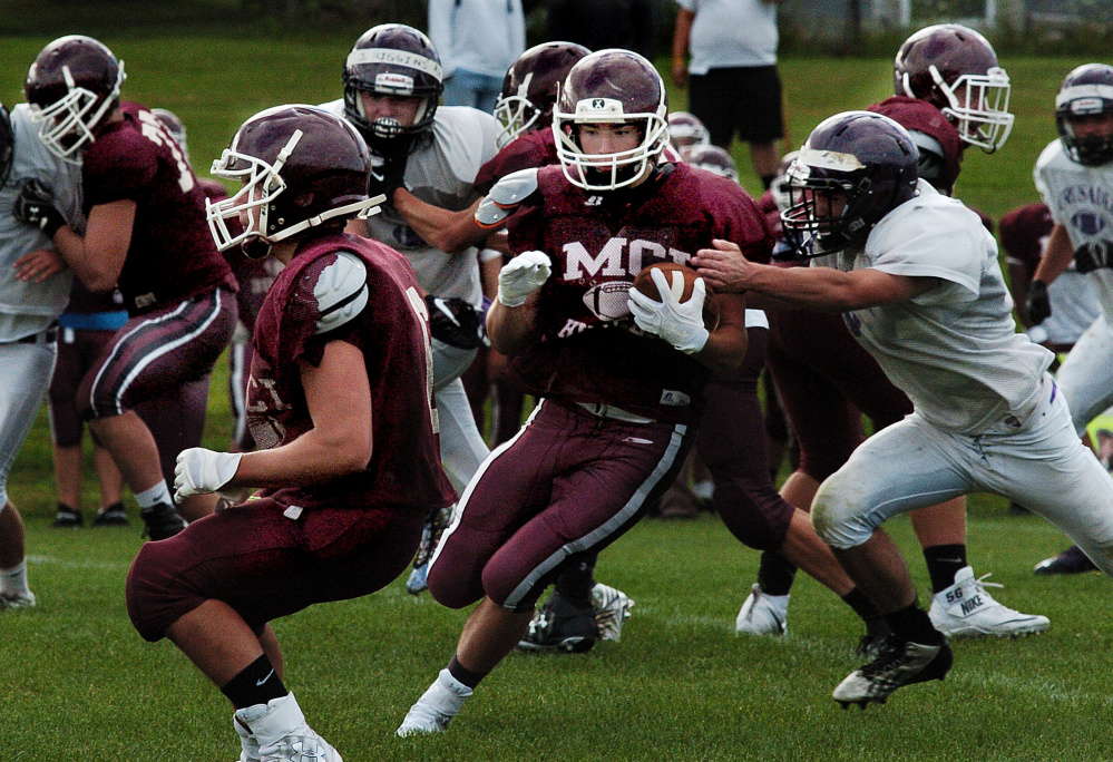 Staff photo by David Leaming   MCI running back Adam Bertrand evades John Bapst defenders during a scrimmage in Pittsfield last week.