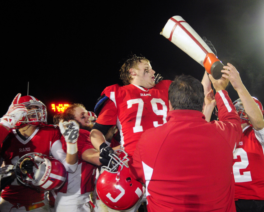 Staff file photo by Joe Phelan   Elijah Tobey and fellow Cony teammates celebrate with the boot after they sank Gardiner in the annual rivalry game last season.