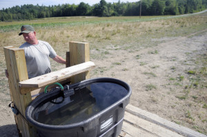 Pete Kelley repairs a water trough in a pasture Tuesday at Kelley Bros. Farm in Pittston. The spring the beef cattle drank from dried up two months ago, compelling Kelley to build a pipeline from a well to provide the herd water.