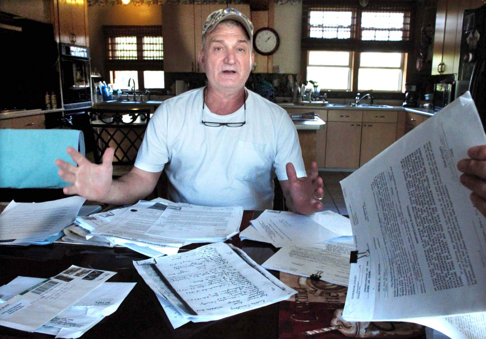 Surrounded by documents and legal papers, Rome resident Peter Fotter talks on Tuesday about a recent dispute with Rome officials regarding access to the Tuttle Cemetery on his property.