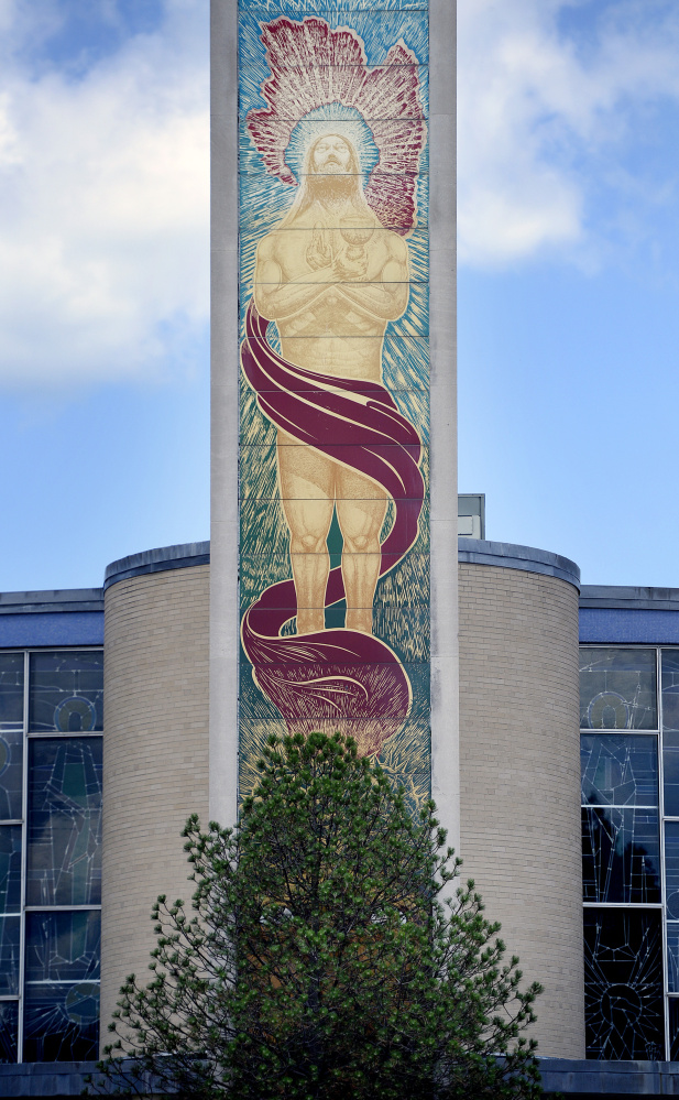 The pine that obscures the mural of Jesus Christ on Holy Cross Catholic Church has started to turn green again.