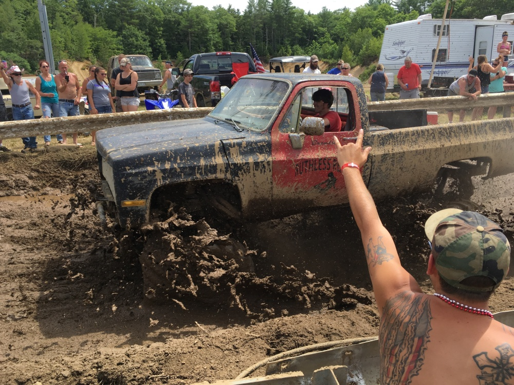 Spectators cheer as a pickup truck splashes through mud Saturday in Hebron. The organizer now calls the event the