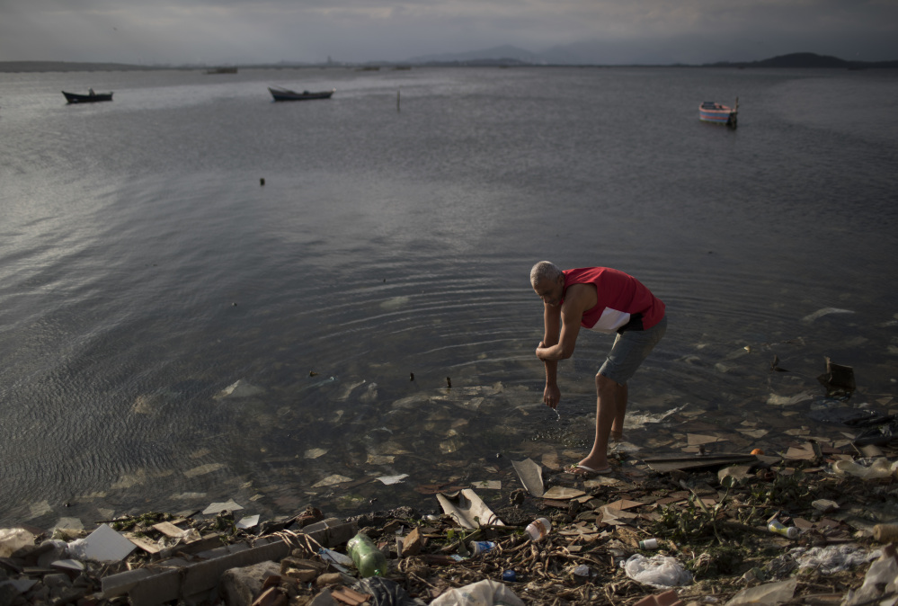 """A man washes himself in the polluted waters of Guanabara Bay in Rio de Janeiro, Brazil, on Saturday. While authorities including Mayor Eduardo Paes have acknowledged the failure of the city's water cleanup efforts, calling it a """"lost chance"""" and a """"shame,"""" Olympic officials insist that Rio's waterways will be safe for athletes and visitors."""