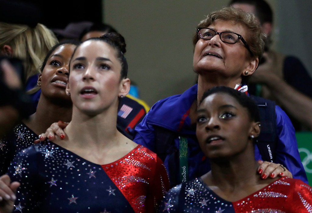Marta Karolyi, U.S. gymnastics team coordinator, looks at the scoreboard along with, from right, Simone Biles, Aly Raisman and Gabrielle Douglas during the artistic gymnastics women's qualification Sunday.