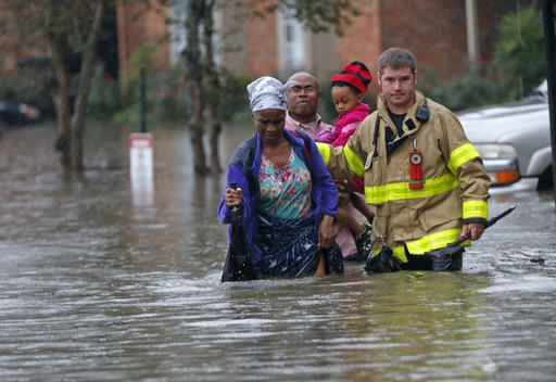 A member of the St. George Fire Department assists residents as they wade through floodwaters from heavy rains in Baton Rouge, La., on Friday.  AP Photo/Gerald Herbert