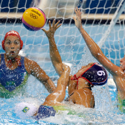 United States' Maggie Steffens passes the ball forward as Brazil's Viviane Bahia, right, and Camila Pedrosa go to block during their women's water polo quarterfinal match.