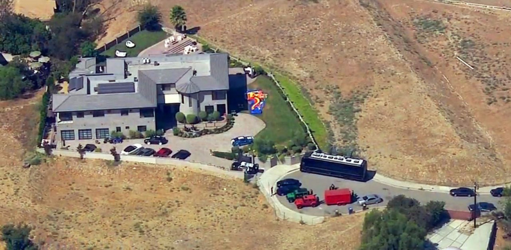 The home of entertainer Chris Brown with police vehicles outside, in the Tarzana area of Los Angeles Tuesday, Aug. 30, 32016. Authorities waited for a search warrant outside Brown's Los Angeles home after getting a woman's call for help, officials said. KABC-TV video image via AP