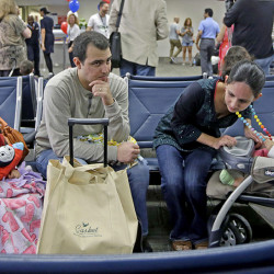 Mario Martinez and his wife Nimaris Niebla wait with their children to depart Fort Lauderdale-Hollywood International Airport in Fort Lauderdale, Fla., Wednesday on a flight to Santa Clara, Cuba, to visit their family. Alan Diaz/Associated Press