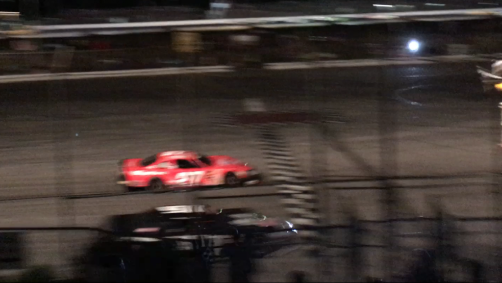 This still image, taken from cell phone video, shows the cars of Wayne Helliwell (orange) and Joey Polewarczyk at the finish line of Sunday night's PASS HP Hood 150 at Oxford Plains Speedway. On Monday morning, the finish was declared a dead heat by series officials.