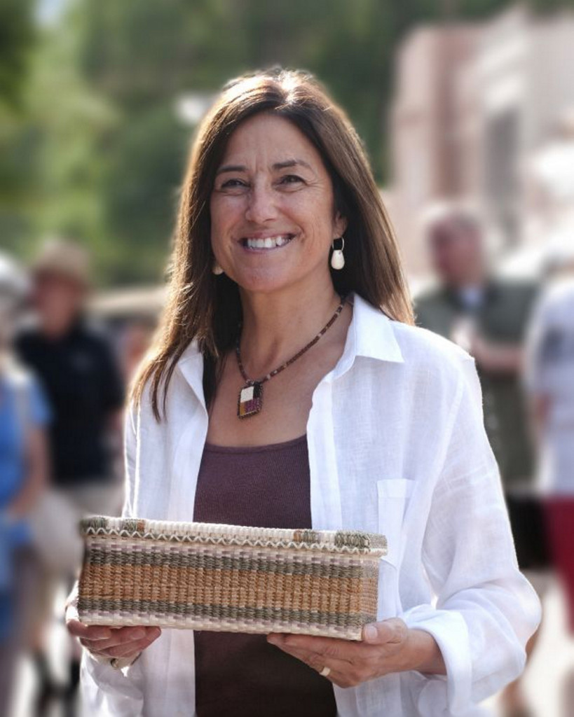 Theresa Secord of Waterville shows one of her baskets at the 2015 Santa Fe Indian Market, a national juried show where she will be exhibiting later this month. (Photo by Steve Wewerka courtesy of the National Endowment for the Arts.)
