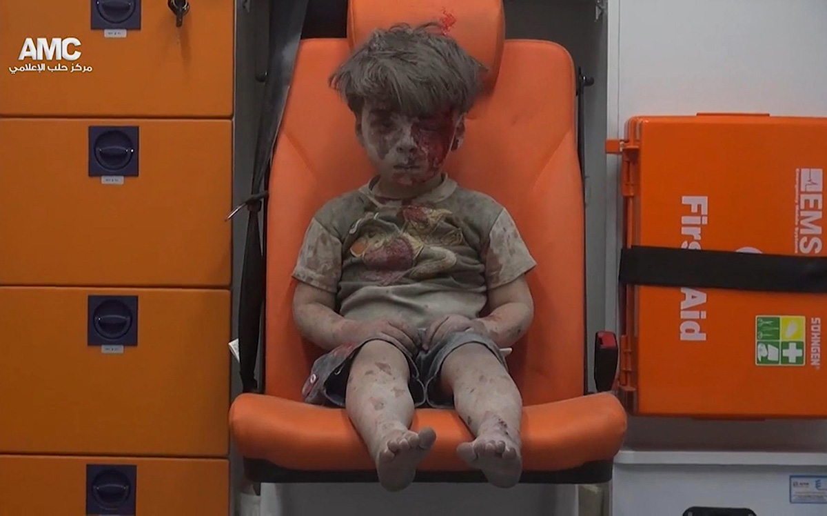 In this frame grab taken from video provided by the Syrian anti-government activist group Aleppo Media Center (AMC), a boy sits in an ambulance after being pulled out of a building hit by an airstirke, in Aleppo, Syria, Wednesday. Aleppo Media Center via AP