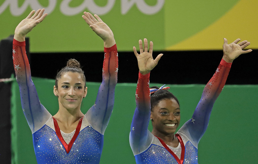 Simone Biles, gold medal winner, and silver medallist and compatriot Aly Raisman, left, wave after final results for floor routine during the artistic gymnastics women's apparatus final at the 2016 Summer Olympics in Rio de Janeiro Tuesday. Dmitri Lovetsky/Associated Press