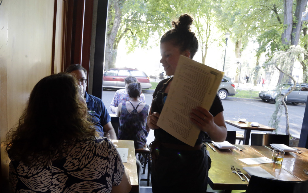 Caroline Pond – a sous chef, server and bartender – talks with customers at Park Kitchen, where shifts were vamped so most employees work full-time and in multiple roles. Nearly all the servers left because of the changes.