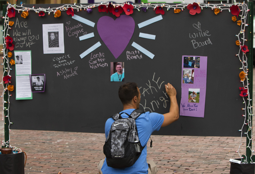 Will Clark of Portland writes the name of a friend he lost 15 years ago to a drug overdose on a memory board in Monument Square. Carl D. Walsh/Staff Photographer