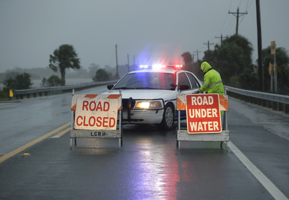 Police block the road to Cedar Key, Fla., as Hurricane Hermine nears the Florida coast Thursday. Rough surf smashed against docks and boathouses, and people braced for the state's first direct hit from a hurricane in over a decade.