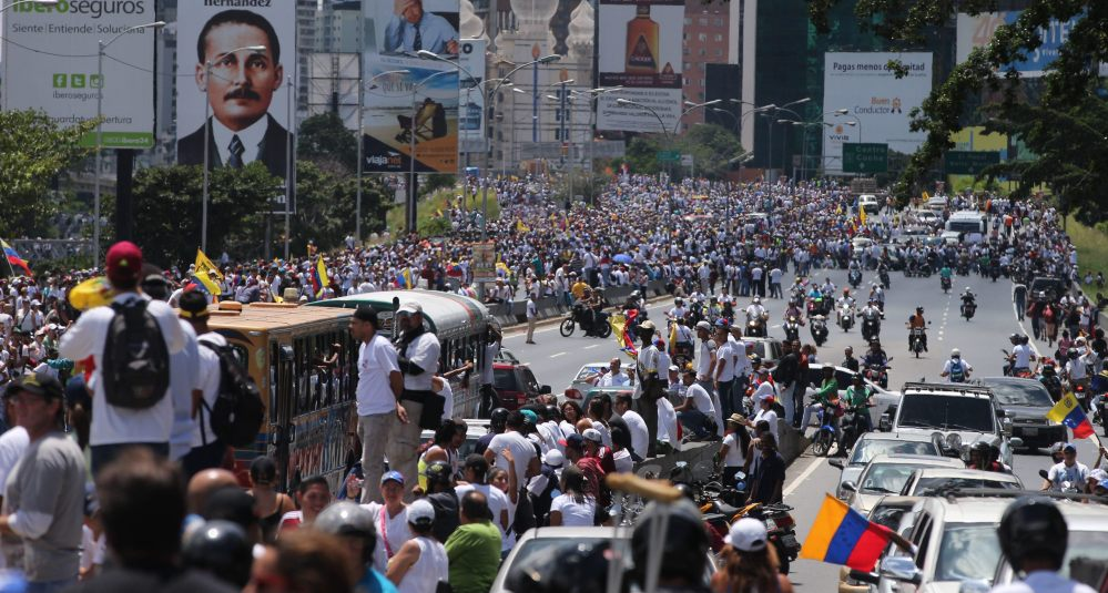 "Demonstrators take part in the  ""Taking of Caracas"" march in Caracas, Venezuela, Thursday, as the opposition vowed to keep up pressure on President Nicolas Maduro"