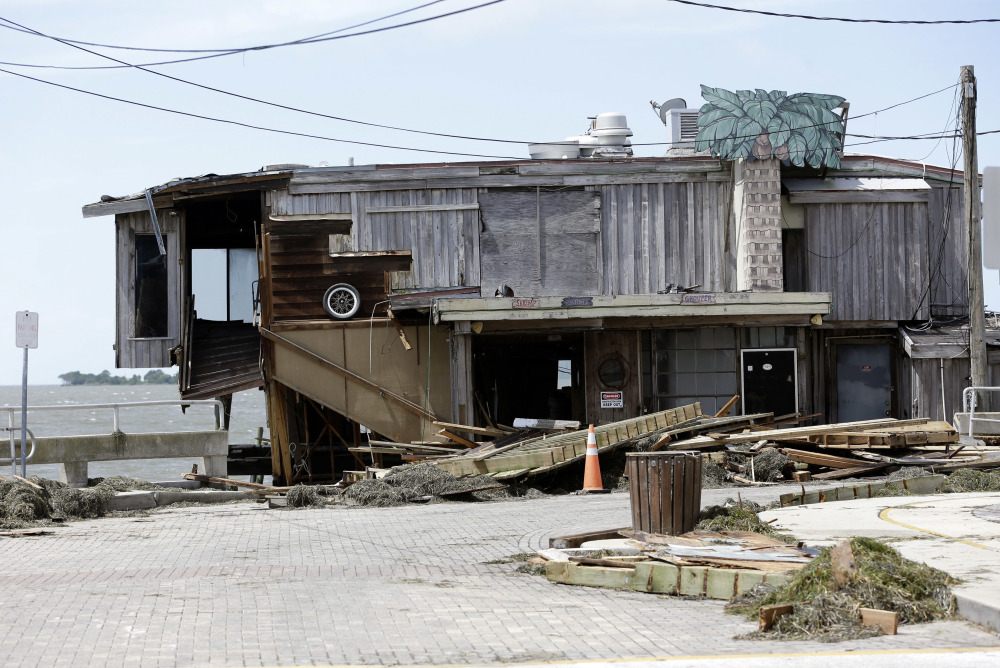Debris lies near a waterfront building damaged by Hurricane Hermine on Friday in Cedar Key, Fla. Hermine was downgraded to a tropical storm after it made landfall, but was expected to strengthen against once it hit the Atlantic Ocean.