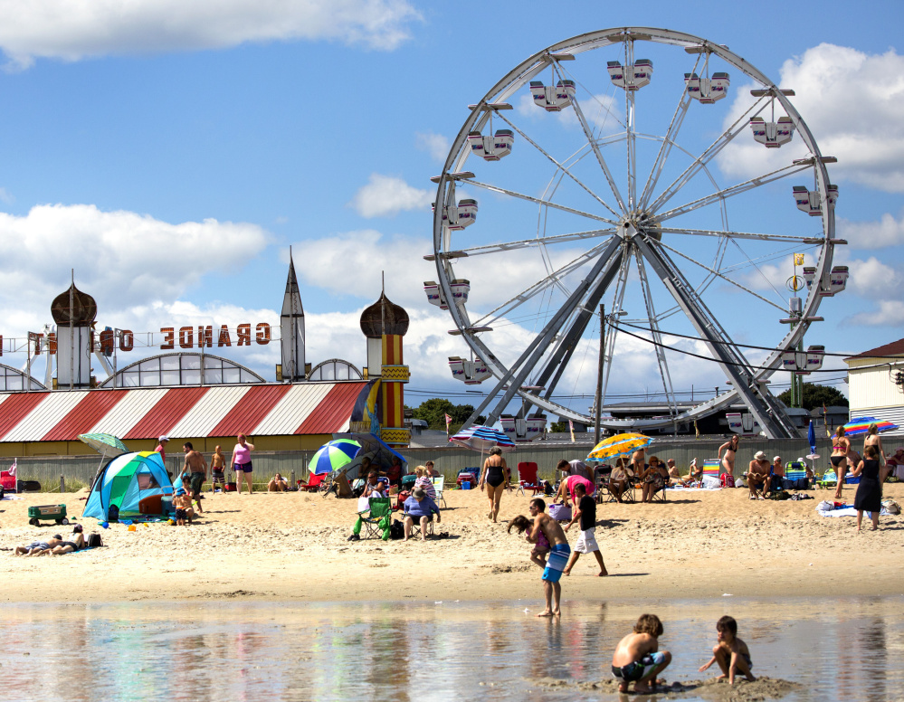 Beachgoers enjoy a beautiful day in Old Orchard Beach. Warm, dry weather has been good for tourism if not for farming.