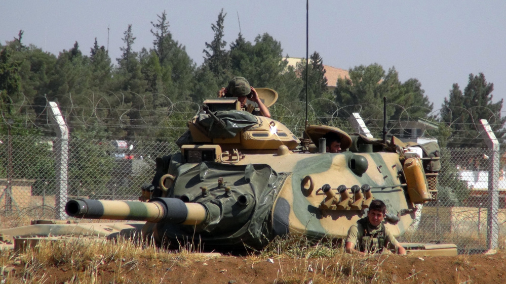 A Turkish army tank is stationed near the Syrian border, in Suruc, Turkey, on Saturday. Turkey's state-run news agency says Turkish tanks have entered Syria's Cobanbey district northeast of Aleppo in a