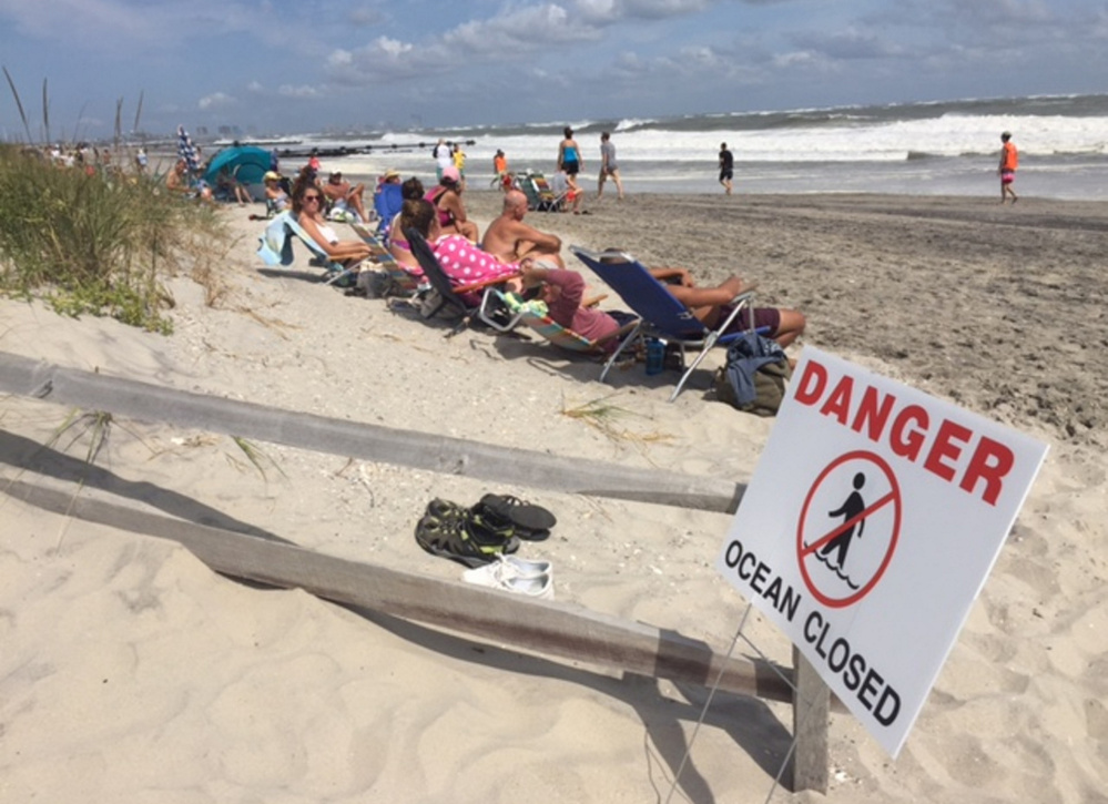 People sit at the beach in Ocean City, N.J., on Sunday as waves roar ashore. Hermine is expected to stay hundreds of miles off the East Coast, delivering large waves and storm surge.
